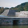 萩城跡。伝統的な防御のための石積み城壁と,指月山を背景に本丸橋の架かった内堀。本丸はその基礎の上に建っていました。