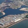 三池港の航空写真。三池港の独特なハミングバード(ハチドリ)の形状とデザインは、有明海東部へに続く航路によって巨大な地形を形作りました。この長い航路は5.5メートルの干満の差を克服し、船舶の移動を円滑、安全にさせるために必要でした。