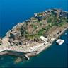 端島の航空写真。周囲の護岸と初期の採炭施設が集中する島の南東部が見える。