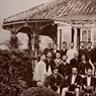 グラバー住宅にてグラバーと三菱の社員。そこは,イギリス・コロニアル様式の,グラバーの住宅兼事務所でした。グラバーは,倒幕を企てた西南雄藩を積極的に支援した人物であり,日本明治期の産業革命において触媒の役割を果たしました。庭にある樹齢300年のソテツは薩摩藩からグラバーに贈られたものです。